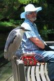 Старший человек при шляпа сидя на стенде на солнечный день Стоковые Фотографии RF