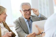 Старший человек пробуя на eyeglasses в оптически магазине стоковые изображения