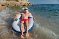 Старший человек плавая в море стоковое изображение