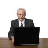 Старший человек сидит на тетради стоковое фото