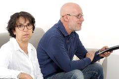 Старший человек смотря ТВ и пробуренная женщина Стоковые Изображения