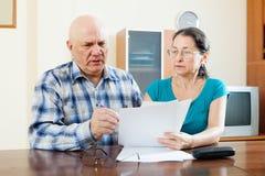 Старший человек с зрелой женщиной заполняет внутри вопросник Стоковое фото RF