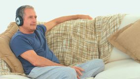 Старший человек слушая к музыке с наушниками сток-видео