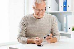 Старший человек с glucometer проверяя уровень сахара в крови стоковые фото