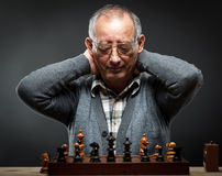 Старший человек думая о его следующем шаге в игре в шахматы Стоковые Фото