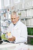 Старший штрихкод скеннирования аптекаря бутылки шампуня на счетчике Стоковая Фотография