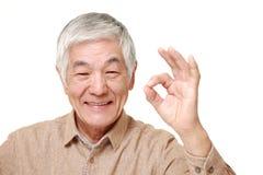 Старший японский человек показывая совершенный знак Стоковые Фото