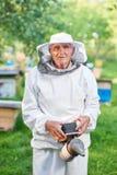 Старший beekeeper работая на его пасеке Стоковые Изображения RF