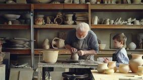 Старший ceramist отливает глину в форму на закручивая бросать-колесе пока его маленький внук наблюдающ и учащ делить видеоматериал