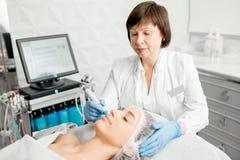 Старший cosmetologist женщины во время процедуры стоковое изображение