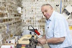 Старший locksmith смотря отсутствующий пока делающ ключ в магазине стоковое фото rf
