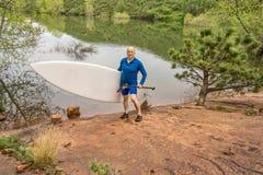 Старший paddler с paddleboard МАЛЕНЬКОГО ГЛОТКА Стоковое фото RF