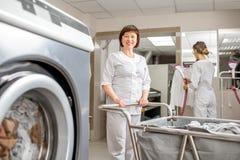 Старший washwoman работая в прачечной Стоковая Фотография