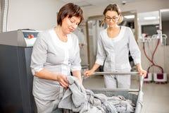 Старший washwoman с ассистентом в прачечной Стоковое Фото