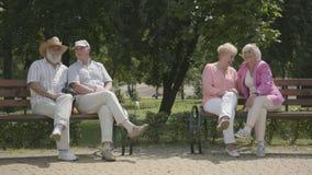2 старших девушки в яркой одежде и мужских друзьях сидя на стенде около одина другого в парке лета сток-видео