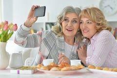 2 старших женщины используя smartphone дома Стоковое фото RF