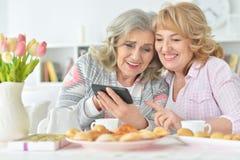 2 старших женщины используя smartphone дома Стоковое Изображение