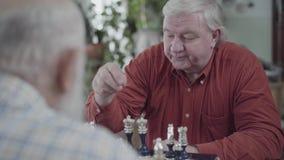 2 старших люд играя усаживание шахмат дома Пухлый человек в красной рубашке делая движение Кавказские друзья соседей стариков акции видеоматериалы