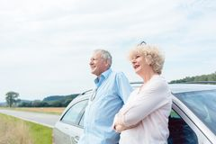 2 старших люд усмехаясь с уверенностью пока полагающся на их автомобиле стоковое изображение