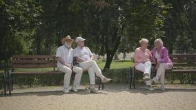 2 старших пары сидя на стенде около одина другого в парке лета Outdoors зрелых людей отдыхая o акции видеоматериалы