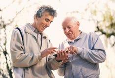 2 старших люд используя умный телефон Стоковые Изображения RF