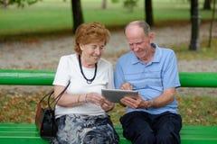 2 старших люд сидя с ПК таблетки Стоковое Изображение RF