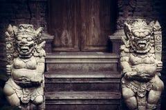 Старые азиатские божества демонов на входе к старому виску с старой деревянной дверью в винтажный стиль стоковое изображение rf