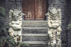 Старые азиатские божества демонов на входе к старому виску с старой деревянной дверью и каменные шаги в винтажный стиль стоковое изображение