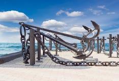 Старые анкеры и анкерные цепи против моря Стоковые Изображения