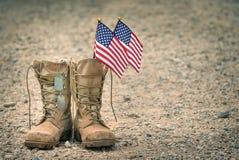 Старые ботинки боя с регистрационными номерами собаки и американскими флагами стоковое изображение