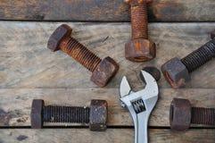Старые болты с инструментами регулируемого ключа на деревянной предпосылке Стоковое Изображение RF