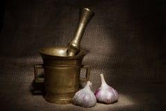 Старые бронзовые миномет и пестик с garliс на предпосылке холста Стоковая Фотография RF