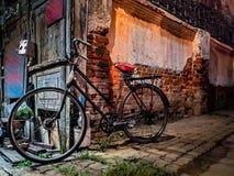 Старые велосипеды припаркованные около старых кирпичных стен Около дороги вечером стоковая фотография