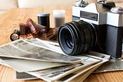 Старые винтажные камера, фильм и фото на деревянном столе стоковые фото