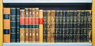 Старые винтажные книги на деревянном Shelfs в библиотеке Стоковое фото RF