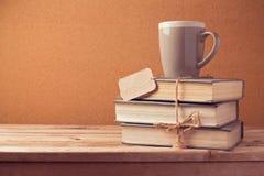 Старые винтажные книги с чашкой и ценником на деревянном столе задняя школа принципиальной схемы к Стоковые Изображения RF