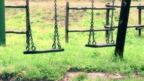 Старые винтажные пустые качания при цепи пошатывая на спортивной площадке для ребенка, двинутой от ветра, стиль замедленного движ сток-видео