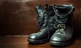 Старые воинские ботинки против деревянной предпосылки стоковое фото