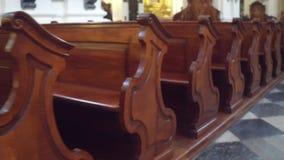 Старые высекаенные деревянные скамьи в видео steadicam католической церкви 4K сток-видео