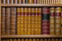 Старые в кожаном переплете книги на полке стоковое фото rf