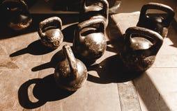 Старые гантели царапины на резиновой поверхности в спортзале в солнечном свете стоковые фото