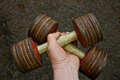 Старые гантели спорт в руке Стоковые Фото