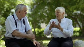 Старые глухой-безгласные пары говоря друг с другом сидеть на стенде в парке лета акции видеоматериалы