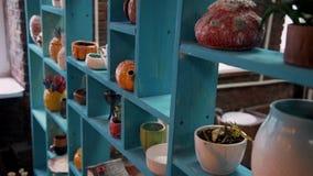 Старые голубые полки с гончарней, блюдами и декоративной вазой сток-видео