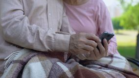 Старые деды наблюдая семейные фото в smartphone, ослабляя в парке, устройство видеоматериал