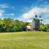 Старые деревянные ветрянки в поле и небе Стоковые Изображения