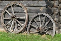 Старые деревянные колеса экипажа на заднем плане деревянной стены дома Стоковое Изображение