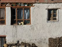 Старые деревянные окна на белой глине огораживают предпосылку, в окнах белых занавесов, на основании стены штабелированный швырок Стоковые Изображения
