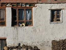 Старые деревянные окна на белой глине огораживают предпосылку, в окнах белых занавесов, на основании стены штабелированный швырок Стоковое Изображение