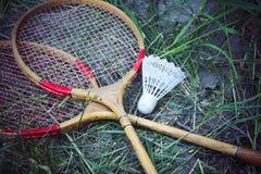 Старые деревянные ракетки и shuttlecock лежа на траве Резвит игры на пикнике стоковое фото rf